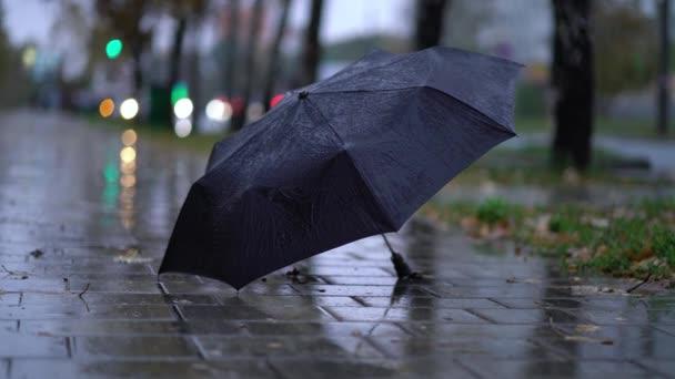 schwarzen Regenschirm an einem regnerischen Tag auf die Straße geworfen