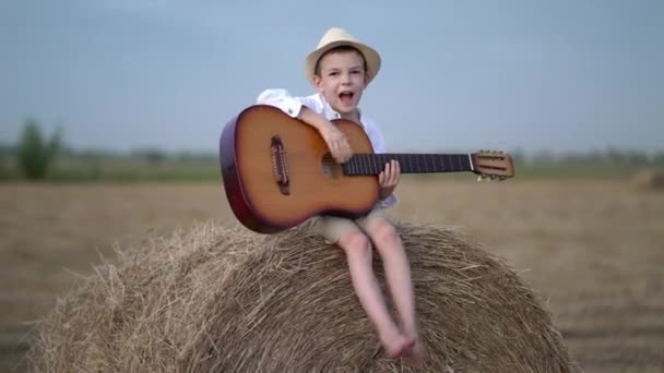 Little boy on a haystack with a guitar