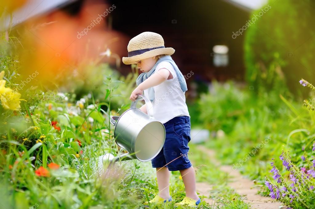 Cute toddler boy in straw hat watering plants in the garden at summer sunny  day — Photo by mary smn c9d4d1a8df14