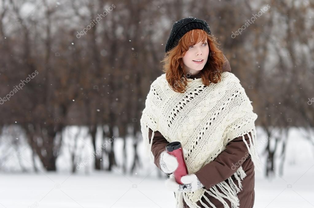 Young beautiful woman walking in winter park