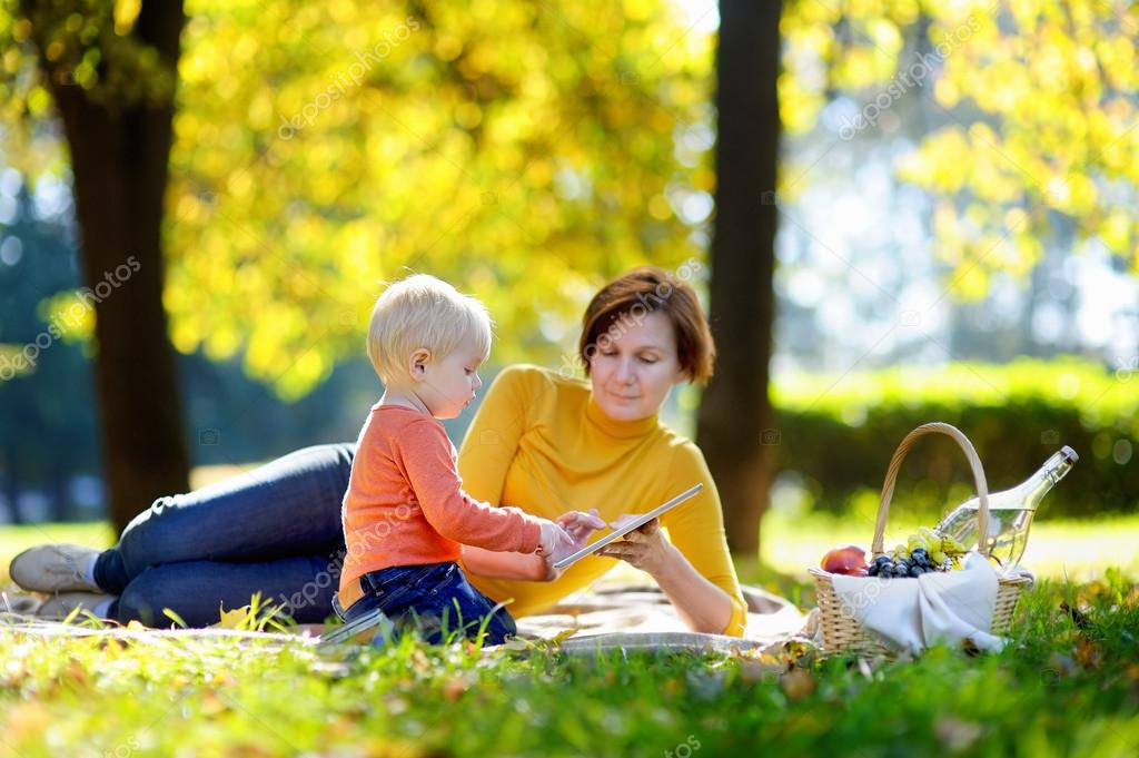 Beautiful woman and her little grandson having a picnic