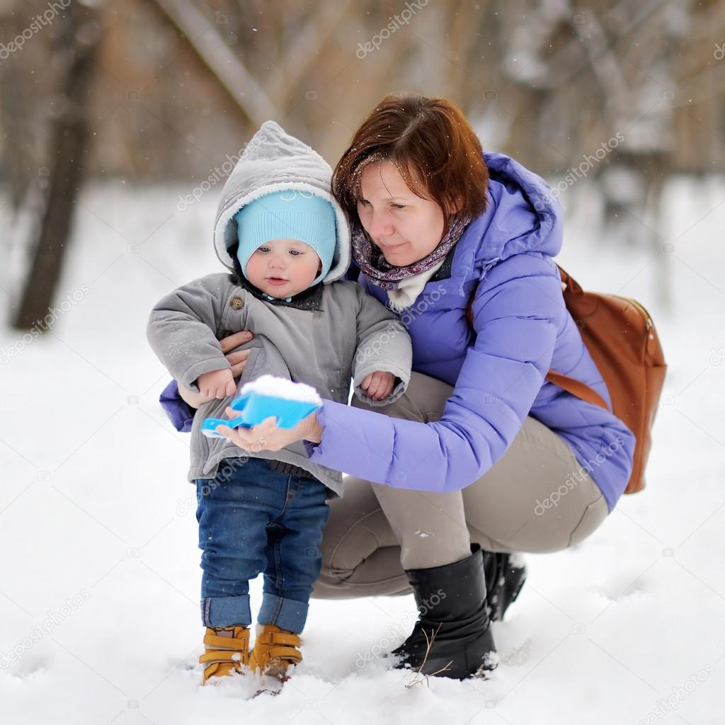 Beautiful woman and her little grandson at the winter