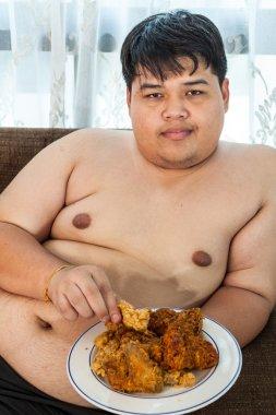 Asian fat man eating fried chicken