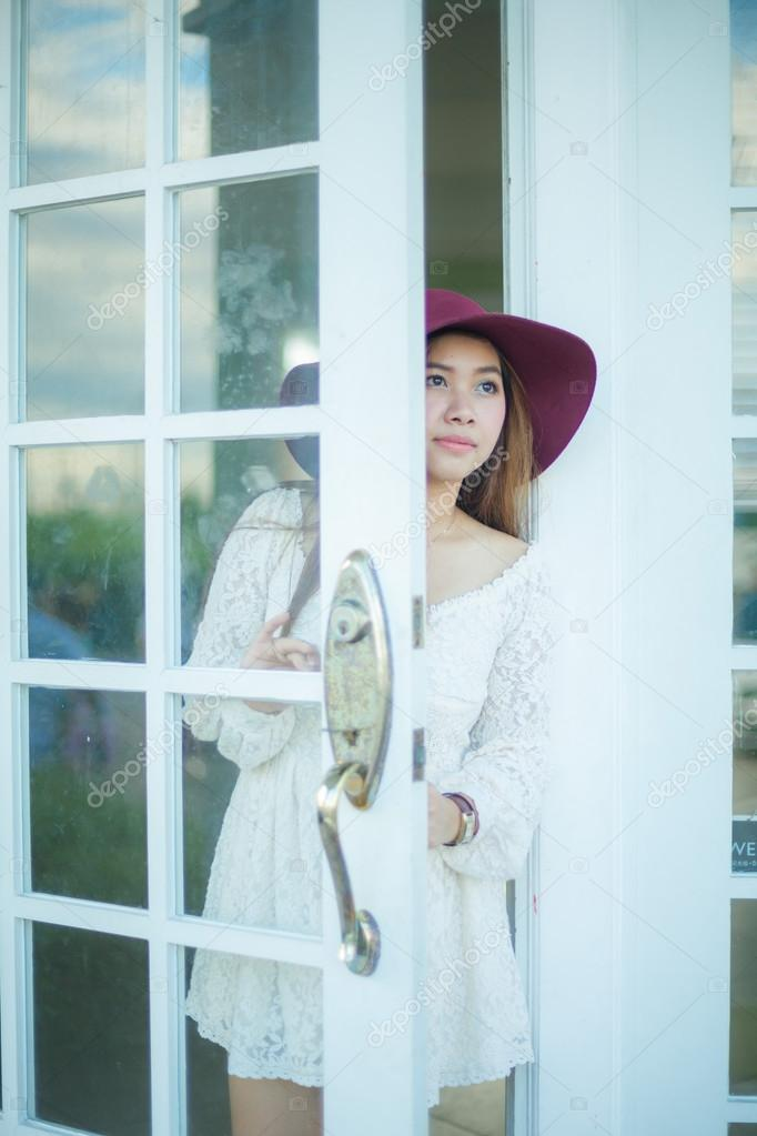 Sad Asian Vintage Woman Looking Out The Door Stock Photo