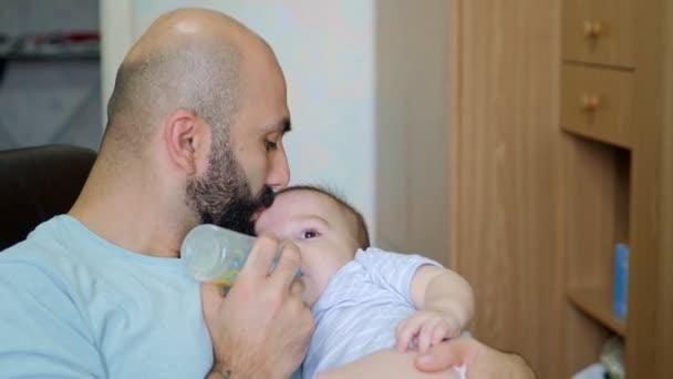Zblízka portrét otce a dítěte. Mladík krmí svého syna z láhve. Péče o děti, Den otců