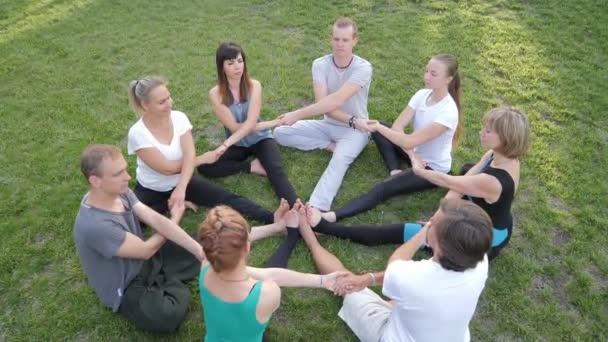 Kreis sportlicher Menschen macht Yoga-Übungen im Park
