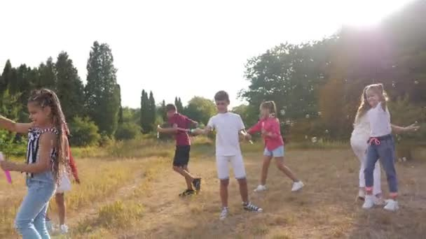 Group of happy kids blow soap bubbles in summer park