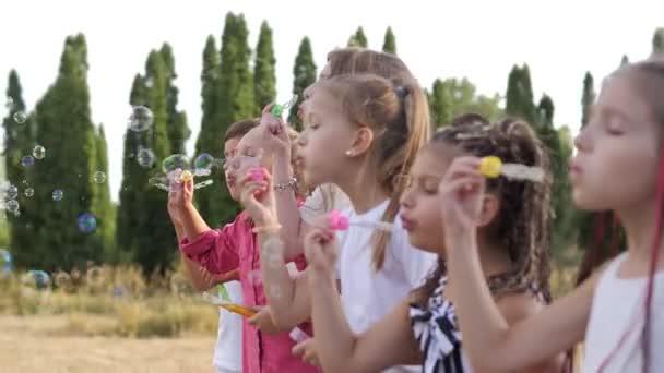 Skupina šťastných dětí foukat mýdlové bubliny v letním parku