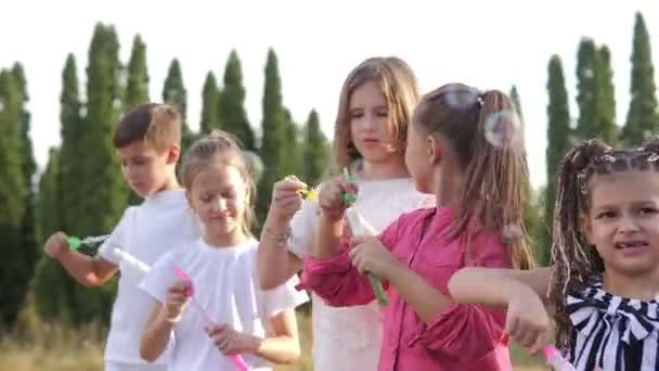 Egy csapat boldog gyerek szappanbuborékot fúj a nyári parkban.