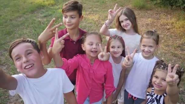 Boldog aranyos gyerekek bámulnak a kamerába a nyári parkban