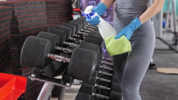 Arbeiterin mit Mundschutz und desinfizierenden Turnschuhen in einem Fitnessstudio während der COVID-19-Epidemie