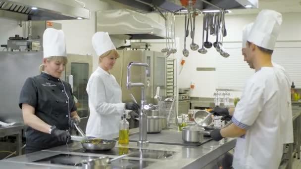 Kuchaři krájejí zeleninu v kuchyni v restauraci