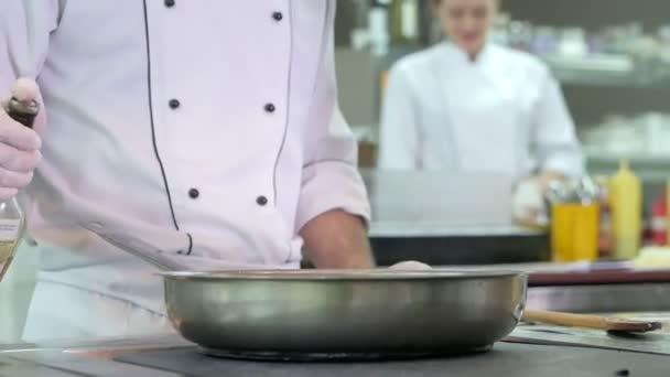 Séf főzés zöldségek serpenyőben az étterem vagy szálloda konyhájában