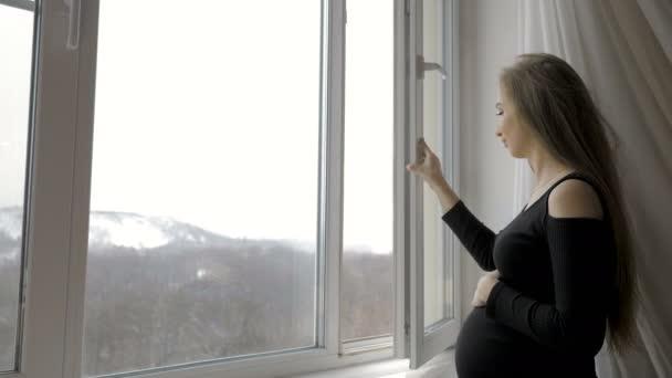 Mladá těhotná žena stojí u okna a drží se za břicho