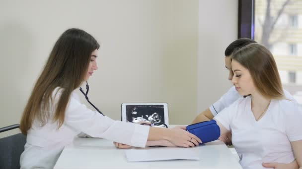 Schwangerschaft. Arzt misst Blutdruck mit medizinischem Manometer und berät junge Paare