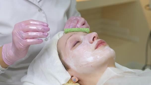 Erfahrene Kosmetikerin trägt Gesichtsmaske auf weibliches Gesicht auf. Mädchen liegen und entspannen. Ihre Augen sind vor Vergnügen geschlossen