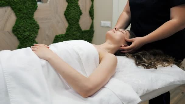 Beautiful young girl doing face and head massage in spa salon. Relax.