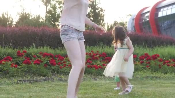 A little 3-year-old sister helps her little brother take his first steps in the park to meet his mother. Mom holds out her hands to her children. Happy family. Happy Kids
