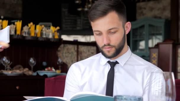 V restauraci, číšník bere pořadí stylový muž v elitní restauraci. zákaznický servis. Číšník, který dává doporučení v restauraci. Klient se seznámí s nabídkou
