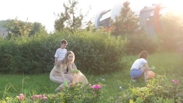 Malé děti se svými matkami za jasného slunečného dne pomáhají čistit část špinavého parku pytli na odpadky. Planeta bez odpadků, bezpečné prostředí. Dobrovolné čištění přírody