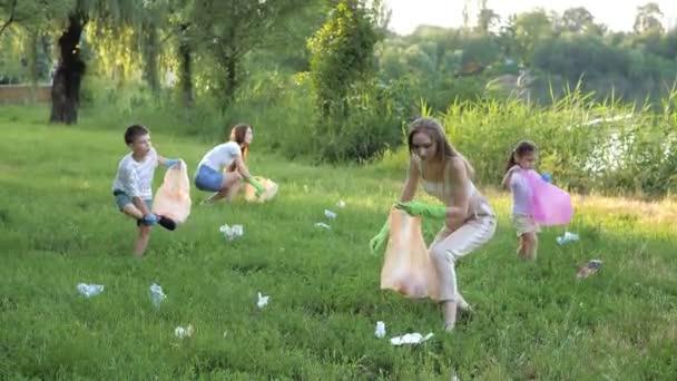 Rodiče a děti dobrovolně čistí park odpadků pytli na odpadky. Koncept planety bez odpadků, bezpečného prostředí. Dobrovolné čištění přírody. Greenpeace. Péče o přírodu