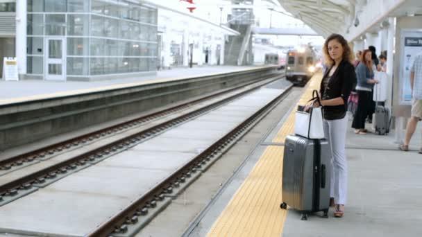 žena s kufrem na platformě na vlakovém nádraží