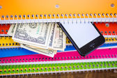 Fotografie Phone, dollars and notebooks, School supplies