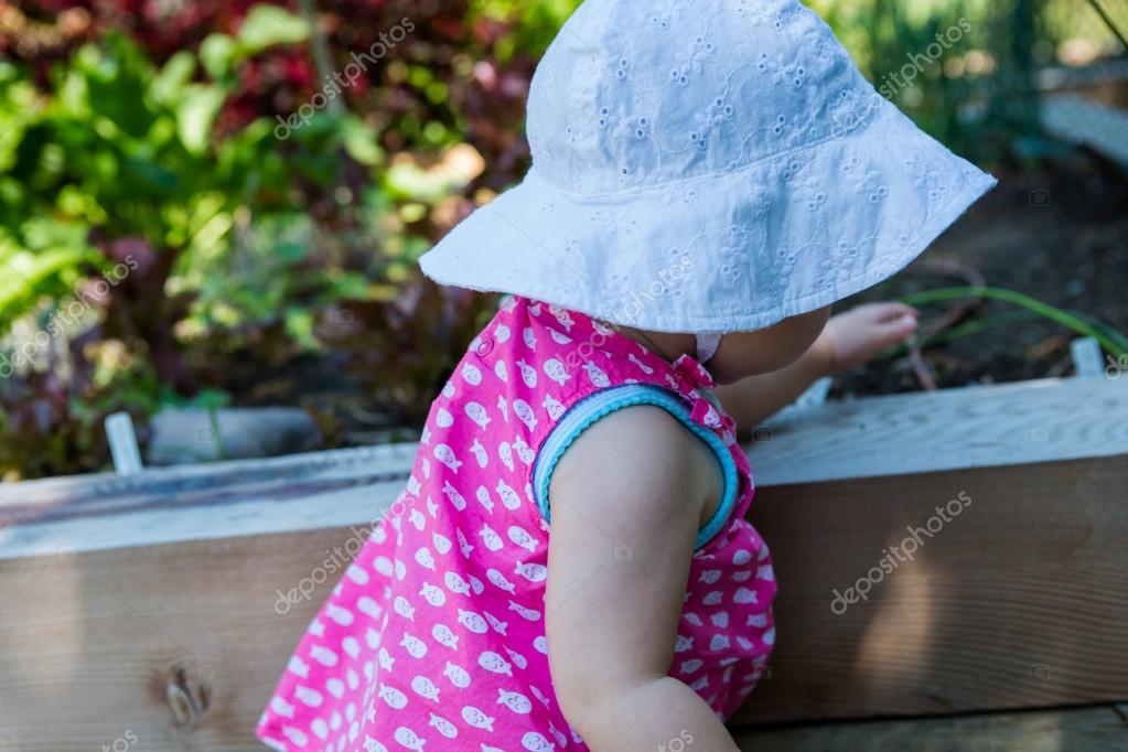 Baby girl in organic urban garden.