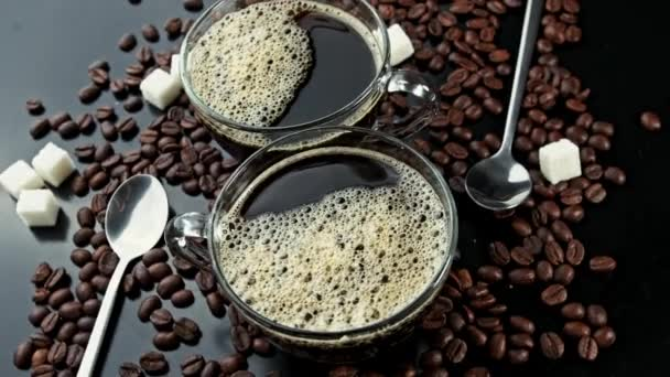 Rotating two cups with coffee on coffee beans and carica sticks