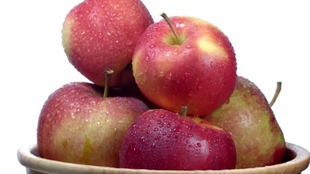 Červená a žlutá jablka na bílém talíři na dřevěné desce se otáčí. 4K