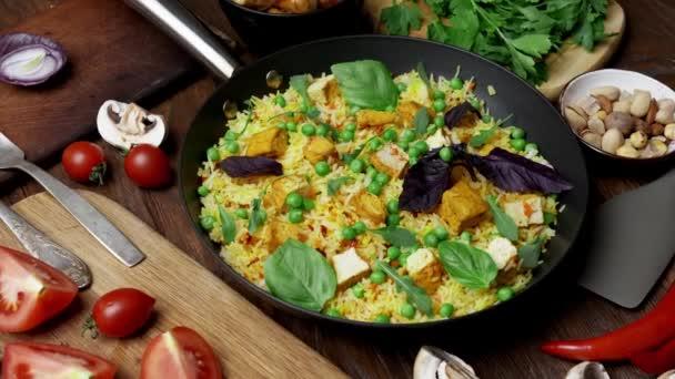 Gemüsereis mit grünen Erbsen, Karotten, Tofu und Pilzen auf Holzgrund. Thema vegetarische Kost
