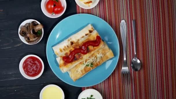 Shawarma sendvič. Čerstvé rohlíky z tenké lavash nebo lavash plněné brambory, houbami, sýrem, mrkví, omáčkou, bylinkami na talíři.