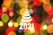 Christmas background-garlands with colorful lights on a decorated Christmas tree, bokeh, Happy New Year 2021 colored symbol and text in trendy flatten style design for seasonal holidays flyers, greetings and invitations cards and christmas themed con