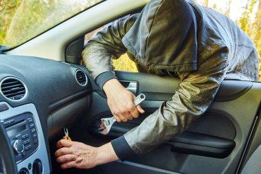 Hooligan breaking into car