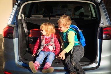 family travel - little boy and toddler girl with luggage in the car