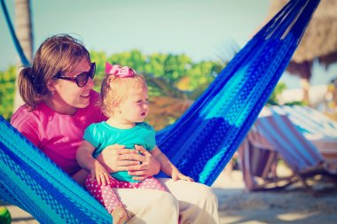 mother and little daughter relaxed in hammock