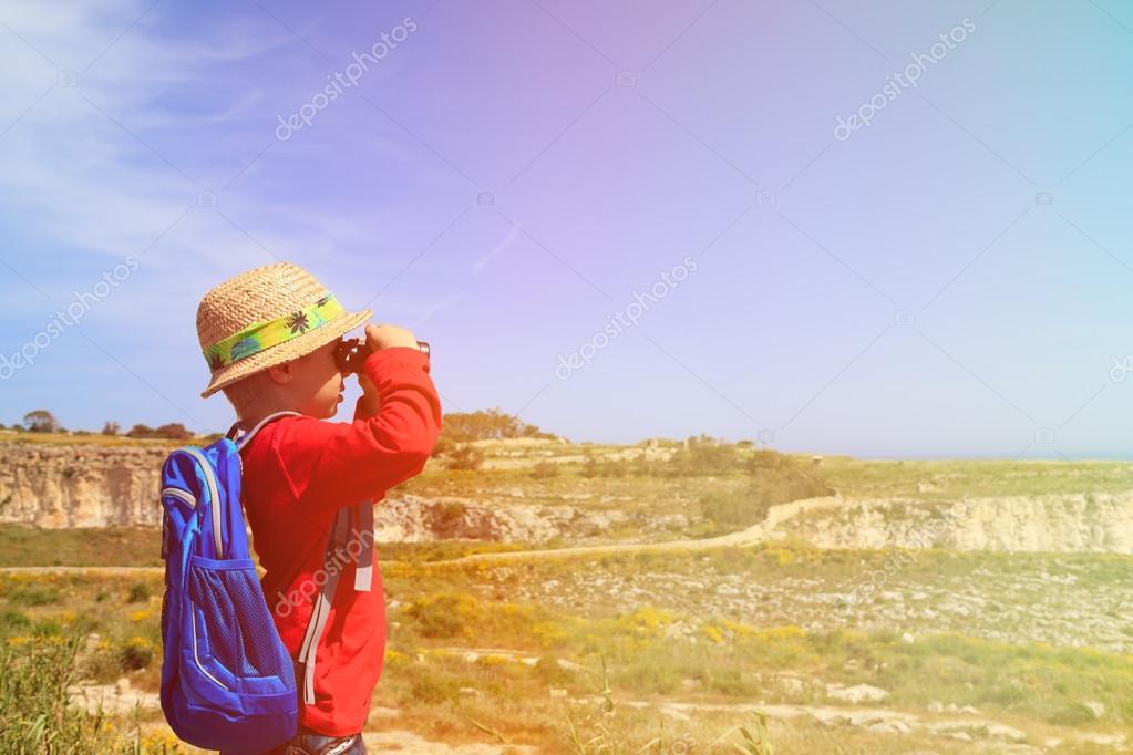 Kleiner junge mit einem fernglas wandern in den bergen