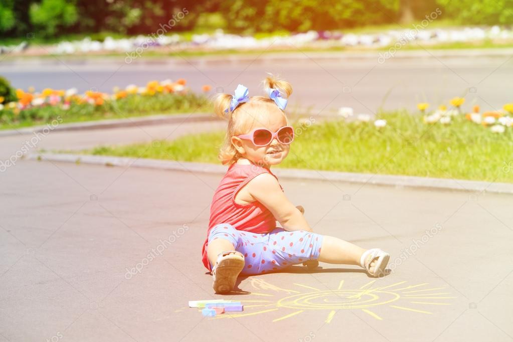 kleines Mädchen mit Kreiden auf einer Straße Zeichnung Sonne ...