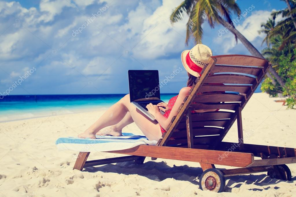 woman with laptop on beach vacation