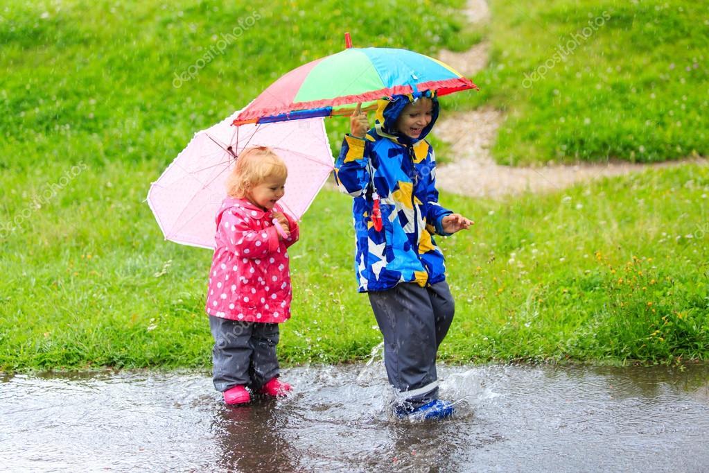 little boy and girl having fun on rain