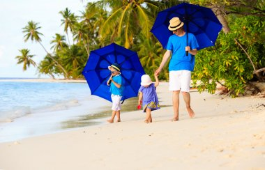 Father and kids at beach with umbrellas to hide from sun