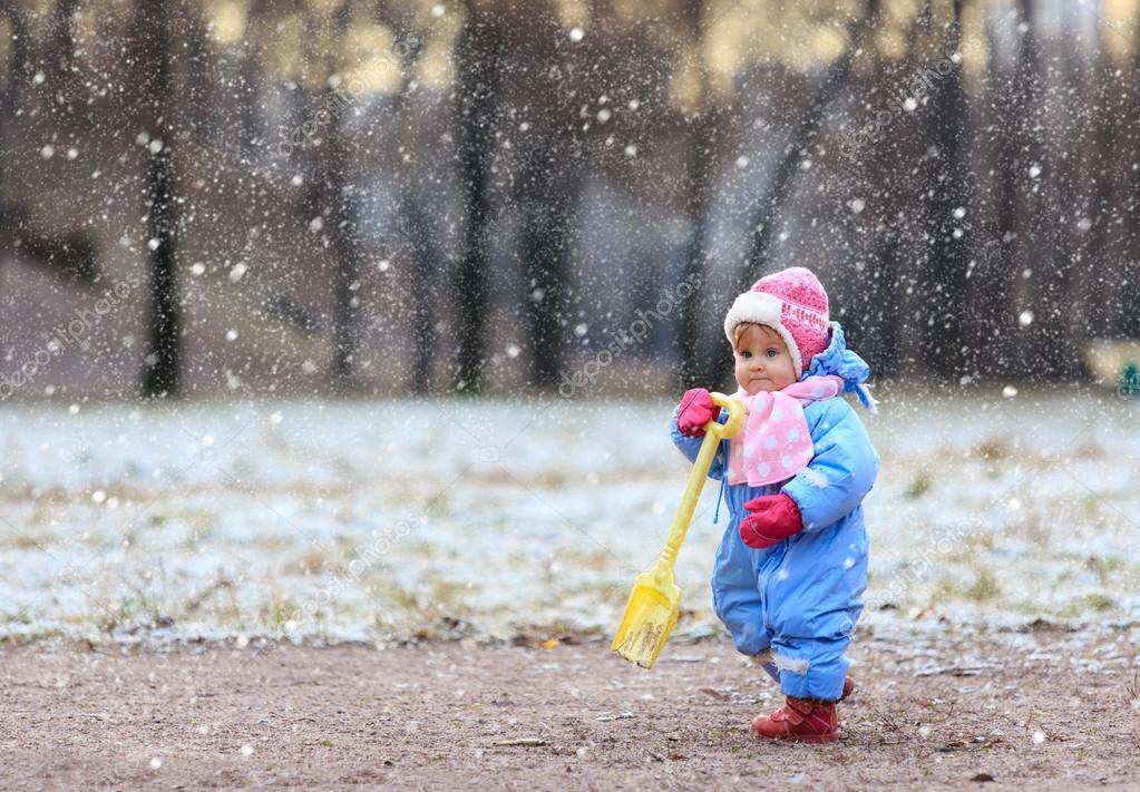 little girl making first steps in winter park