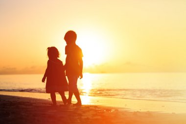 little boy and girl walking on sunset beach