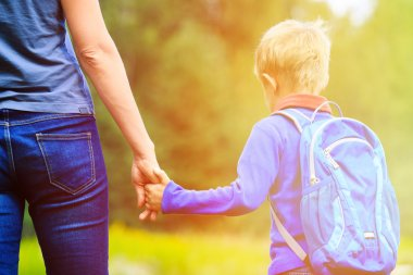 Mother holding hand of little son with backpack outdoors