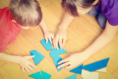 hands of teacher and child playing with geometric shapes
