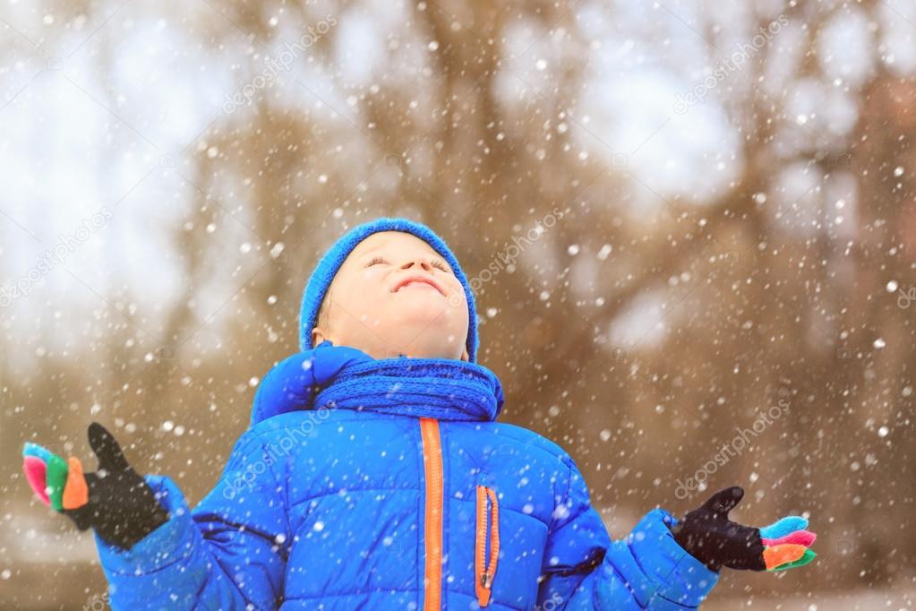 little boy enjoy first snow in winter nature