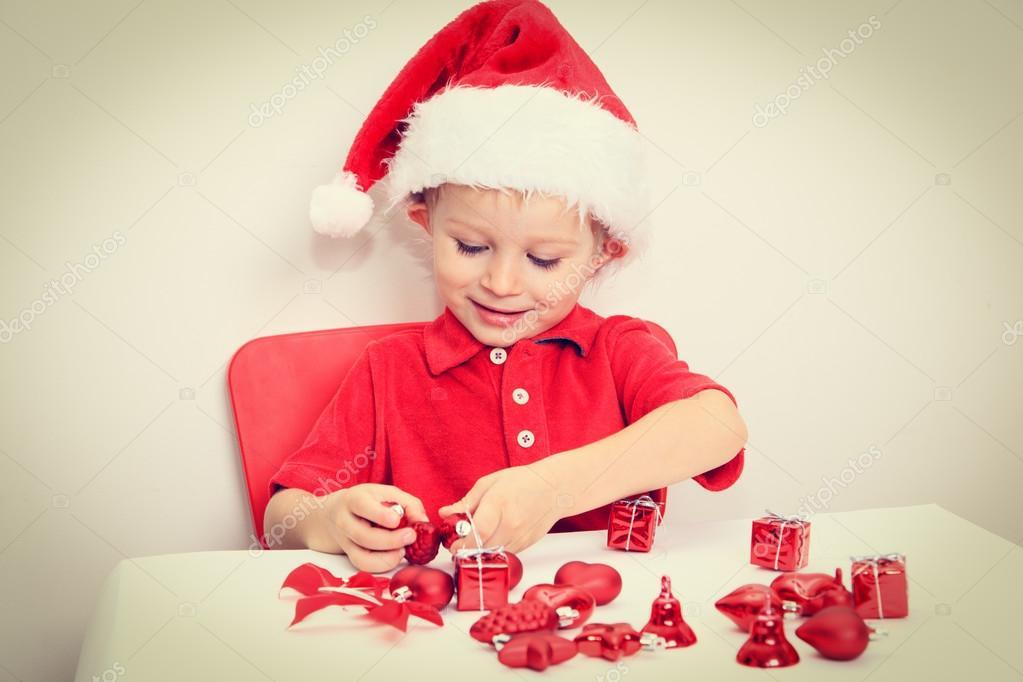 kleine Junge in Nikolausmütze sortieren Weihnachtsgeschenke ...