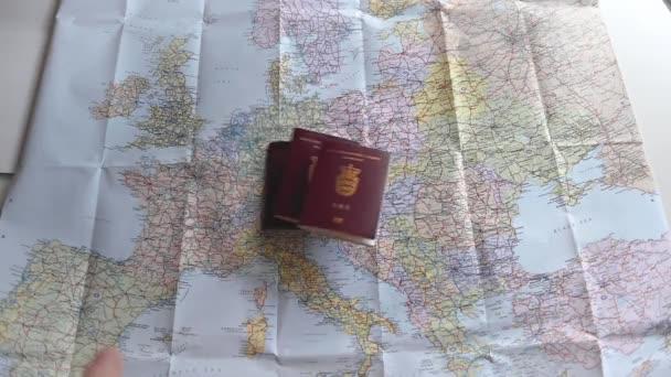 Cestovní pasy a různé měny v plastovém sáčku jsou házeny na barevnou mapu Evropy. Většina Evropy je v rámu. Krátký klip pro ilustraci cestování a cestovního ruchu. Zpomalený pohyb 1080p stock záběry Brian Holm Nielsen