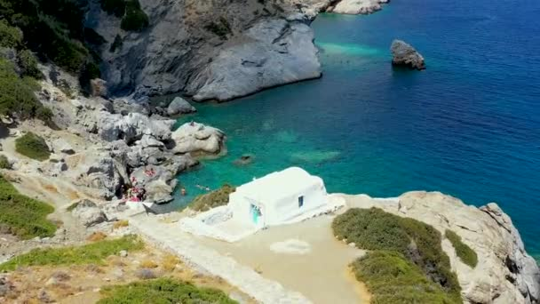 Drone flying over the small rocky beach of Agia Anna Amorgo in Greece. There are people soaking up the sun on the rocks, and people swimming in the beautiful clear blue sea. 1080p