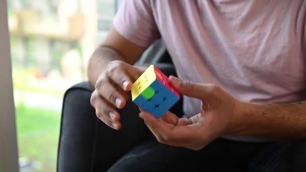Mladý muž sedí v křesle v pohodlí svého domova a řeší 3D puzzle Rubikovy kostky. Tvář není vidět, jen se soustřeď na kostku. Krátký klip